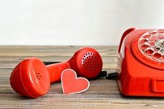 Valentin dagkort: Gammal röd telefon och hjärta formad etikett Arkivbild