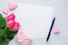 Valentin dagkort med den tomma listan av papper, rosor och pennan fotografering för bildbyråer