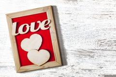 valentin för dag s Ett ord av förälskelse i en dekorativ ram och två hjärtor Begreppet av dagen för valentin` s Royaltyfri Fotografi
