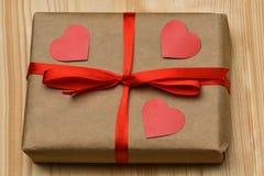 valentin för dag s Gåvaasken i en Kraft bruntpacke är på ett träbräde som binds med ett rött band och är överst, tre sned rött arkivfoto