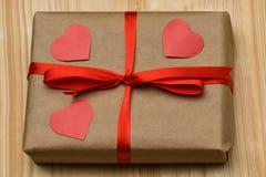valentin för dag s Gåvaasken i en Kraft bruntpacke är på ett träbräde som binds med ett rött band och är överst, tre sned rött royaltyfri foto