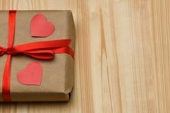 valentin för dag s Gåvaasken i en Kraft bruntpacke är på ett träbräde som binds med ett rött band och är överst, två sned rött arkivfoton