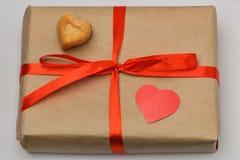 valentin för dag s Gåvaasken på en grå bakgrund i en Kraft bruntpacke binds med ett rött band och är överst ett snidit beträffand arkivfoto