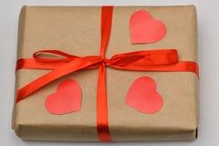 valentin för dag s Gåvaasken på en grå bakgrund i en Kraft bruntpacke binds med ett rött band och är överst tre sned rött arkivfoto