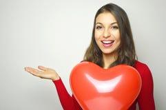 valentin för dag s Härlig ung kvinna som bär den röda klänningen och innehavet en röd hjärtaluftballong som visar din produkt ell Arkivfoton