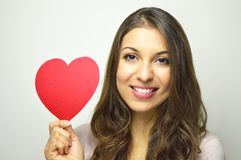 valentin för dag s Härlig ung kvinna som rymmer en pappers- hjärta och leende på kameran på grå bakgrund Arkivbilder