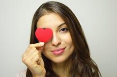 valentin för dag s Härligt förälskat innehav för ung kvinna en litet pappers- hjärta och leende på kameran på grå bakgrund Fotografering för Bildbyråer