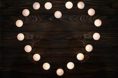 valentin för dag s Hjärtan av brinnande stearinljus på en träbakgrund Kraft papper med kopieringsutrymme för feriehälsningar royaltyfria foton