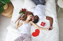 valentin för dag s lyckliga par med blommor i säng arkivfoto