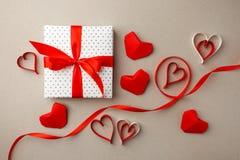 valentin för dag s Sammansättning som göras av gåvan, origamihjärtor och band på grå bakgrund Hjärta för två rosa färg Lekmanna-  arkivfoto