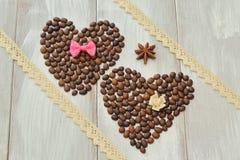 valentin för dag s Två hjärtor gjorde av kaffebönor med flugan och den dekorativa blomman som gjordes av satäng, stjärnaanis och, fotografering för bildbyråer
