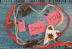 Valentin hälsningkort med bruna kaffehjärtor, rött band, Arkivfoto