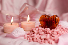 Valentin heart. A detail of a transparent heart of red glass with stripes on a pile of little pink stones, two burning candles and flower petals in the Royalty Free Stock Image