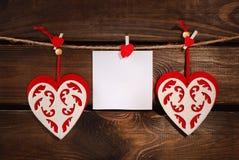 Valentin klädde med filt hjärtor och kortet på träbakgrund arkivfoton
