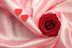 Valentin Love Rose - Red. Valentine's Day theme - a detail of a red rose and two little red hearts lying on pink satin fabric Stock Photography