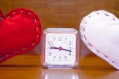 Valentin röda och vita hjärtor för dag - och en klocka Arkivbild