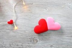 Valentin rosa och röda hjärtor för dag med dekorativt ljus på träbakgrund arkivbilder