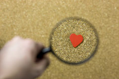 Valentin - single. Valentin theme - a detail of a red heart on a cork background and a hand with magnifying glass - lonely person looking for love Stock Images