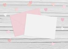 Valentindag eller bröllopmodellplats med kuvertet, det tomma kortet, pappers- hjärtakonfettier och träbakgrund Royaltyfria Bilder