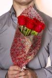 Valentindag eller förslag Ung lycklig stilig man som rymmer den stora gruppen av röda rosor i hans hand på grå bakgrund arkivbild