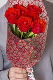 Valentindag eller förslag Ung lycklig stilig man som rymmer den stora gruppen av röda rosor i hans hand på grå bakgrund arkivbilder