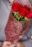 Valentindag eller förslag Ung lycklig stilig man som rymmer den stora gruppen av röda rosor i hans hand på grå bakgrund royaltyfri foto