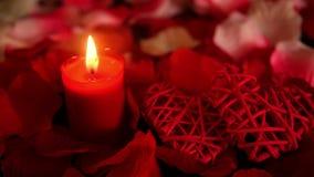 Valentindag med längd i fot räknatgarneringhjärta, stearinljusbränning och roskronblad