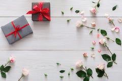 Valentindagbakgrund, gåvaaskar och blommor på vitt trä royaltyfri foto