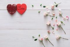 Valentindagbakgrund, hjärtor och blommor på vitt trä royaltyfri foto