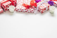 Valentindagbakgrund med gåvaaskar med hjärtor formar pappersomslaget och rosor på vit bakgrund arkivfoto