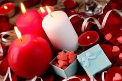 Valentindagbakgrund med gåvaboxe, stearinljus, rosa kronblad, röd hjärta Royaltyfri Foto