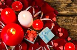 Valentindagbakgrund med gåvaboxe, stearinljus, rosa kronblad, röd hjärta Fotografering för Bildbyråer