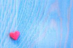 Valentindagbakgrund med shugar valentinhjärta på den blått målade wood tabellen retro filter Arkivfoton