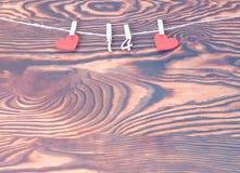 Valentindagbegrepp, hälsningkort Röda trähjärtor med ben med diagram av FEBRUARI 14 som hänger på rep på träbakgrund Royaltyfria Bilder