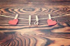 Valentindagbegrepp, hälsningkort Röda trähjärtor med ben med diagram av FEBRUARI 14 som hänger på repet på brunt trä Royaltyfria Bilder