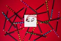 Valentindaghjärta som göras av rött pråligt drev på vitbok på röd bakgrund med kontorsblyertspennor Valentin dagkort, orientering royaltyfri bild