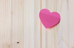 Valentindagkort med den klibbiga anmärkningen i formen av en hjärta på en träbakgrund Arkivfoton