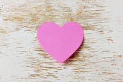 Valentindagkort med den klibbiga anmärkningen i formen av en hjärta på en träbakgrund Arkivbild
