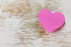 Valentindagkort med den klibbiga anmärkningen i formen av en hjärta på en träbakgrund Royaltyfria Bilder
