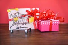 Valentindagshopping och ask för vagn för shopping för ask för gåva för gåvakort rosa närvarande med det röda kortet för bandpilbå royaltyfri bild