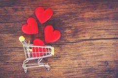 Valentindagshopping och röd hjärta på förälskelse för shoppingvagn som shoppar ferie för förälskelsevalentindag på träbakgrund royaltyfria bilder