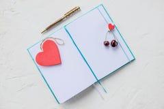 Valentindagstilleben med pennan, hjärta och garneringar Anteckningsbok med hjärta som isoleras på vit tom dagbok med en hjärta royaltyfri fotografi