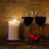 Valentindagvykort: romantisk inre med vinexponeringsglas, stearinljuset och röd hjärta Royaltyfria Foton