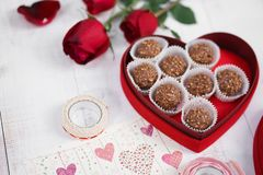 Valentine`s day. Nutty chocolate in a red heart box and red roses for Valentine`s or anniversary present. Soft focus on the nutt royalty free stock image