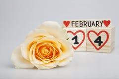 Valentine's dagsammansättning med gulingrosen och träkalendern Arkivbild