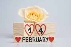 Valentine's dagsammansättning med träkalender- och gulingrosen Fotografering för Bildbyråer