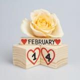 Valentine's dagsammansättning med träkalender- och gulingrosen Arkivfoto