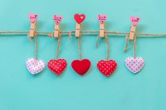 Valentine's Day.  Sewed pillow hearts row border on red, pink and white clothespins at rustic blue pastel wall. Stock Image