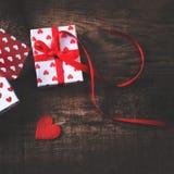 Valentine's-Tageskarte mit roten Herzen, Geschenkbox mit rotem Band Stockfotografie