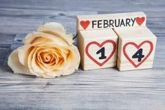 Valentine's-Tageszusammensetzung mit hölzerner Kalender- und Gelbrose Stockfotografie